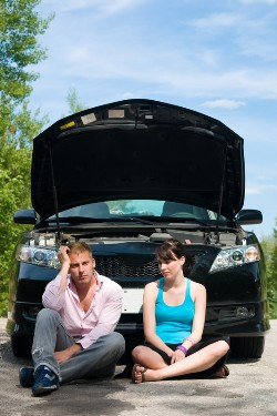 Couple in front of a broken down car on the side of the road.